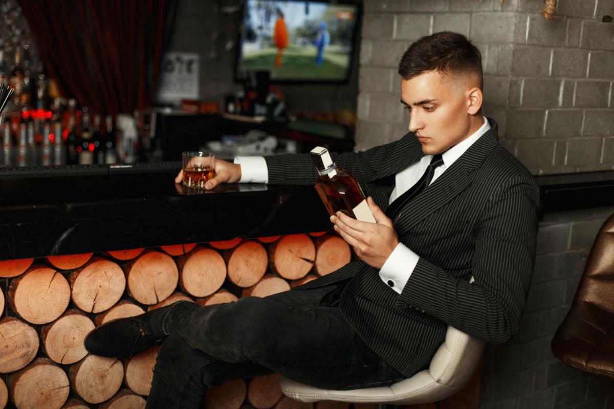 hombre joven botella alcohol traje