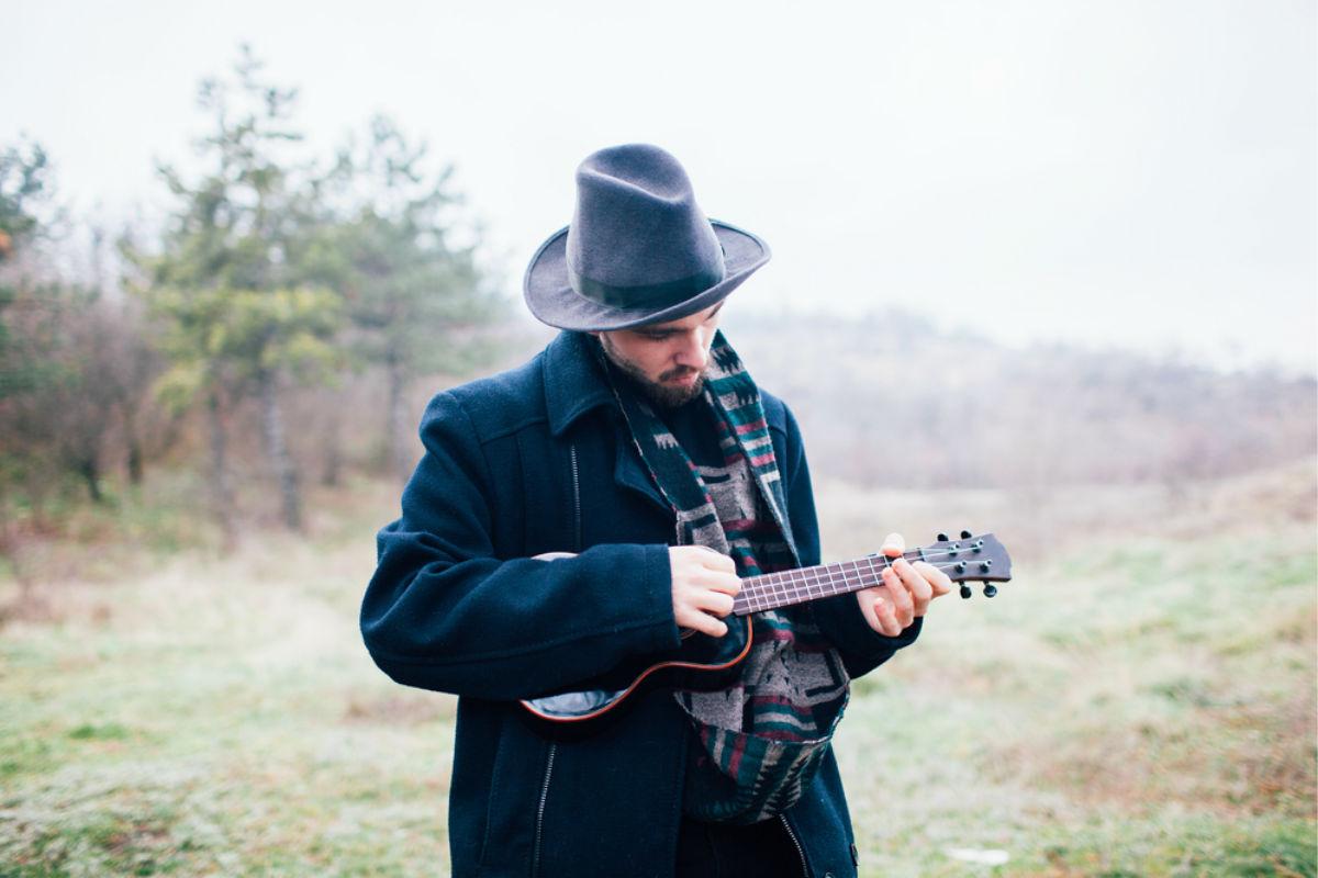 hombre sombrero bohemia guitarra invierno